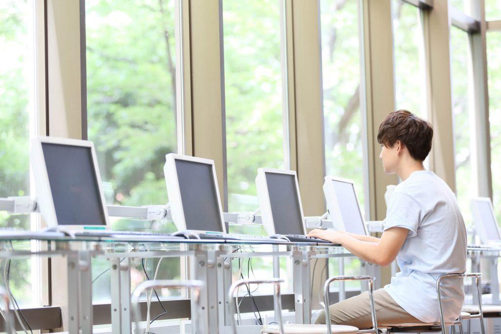ネットカフェで就活する若い男性
